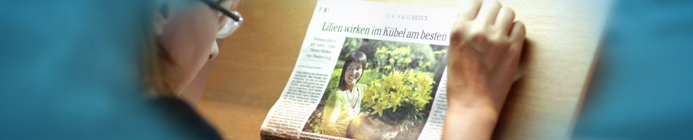 Frau mit Brille liest Zeitung mit Sehhilfe