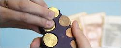 Hand mit Münzbox vor Geldscheinen